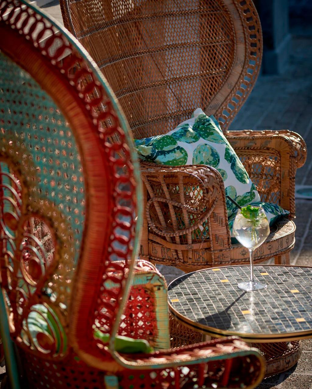 Overdekt terras met pauwenstoelen en vrolijke kussens