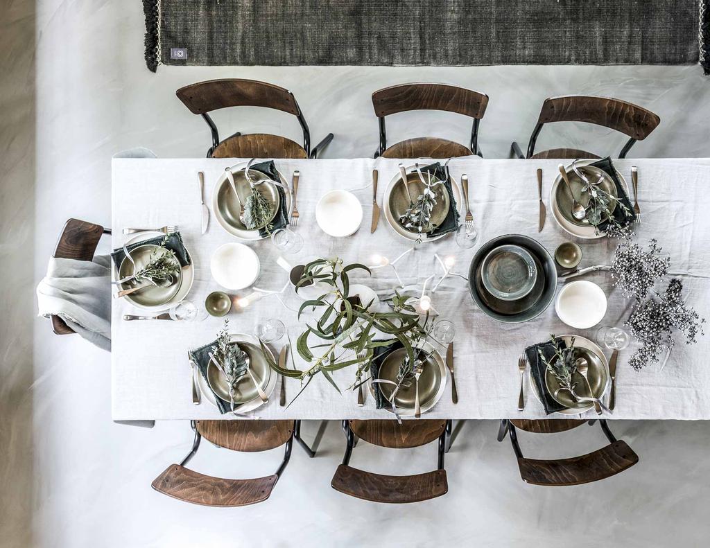 Gedekte tafel met opvallend servies op een wit laken