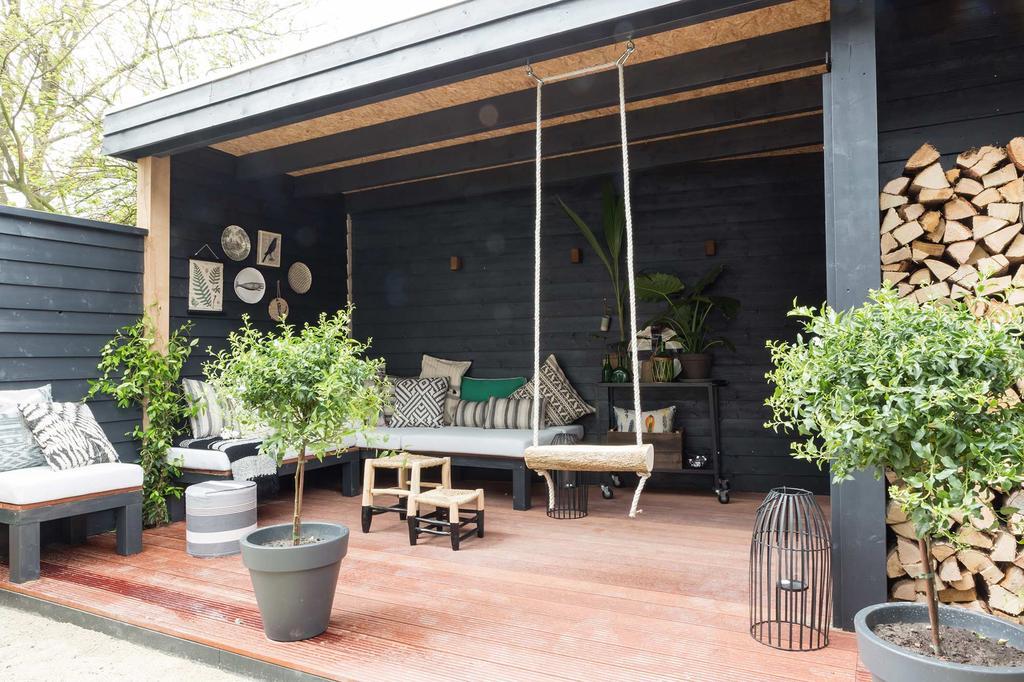 Open veranda in de tuin met schommel, zetels en kleine bijzettafeltjes