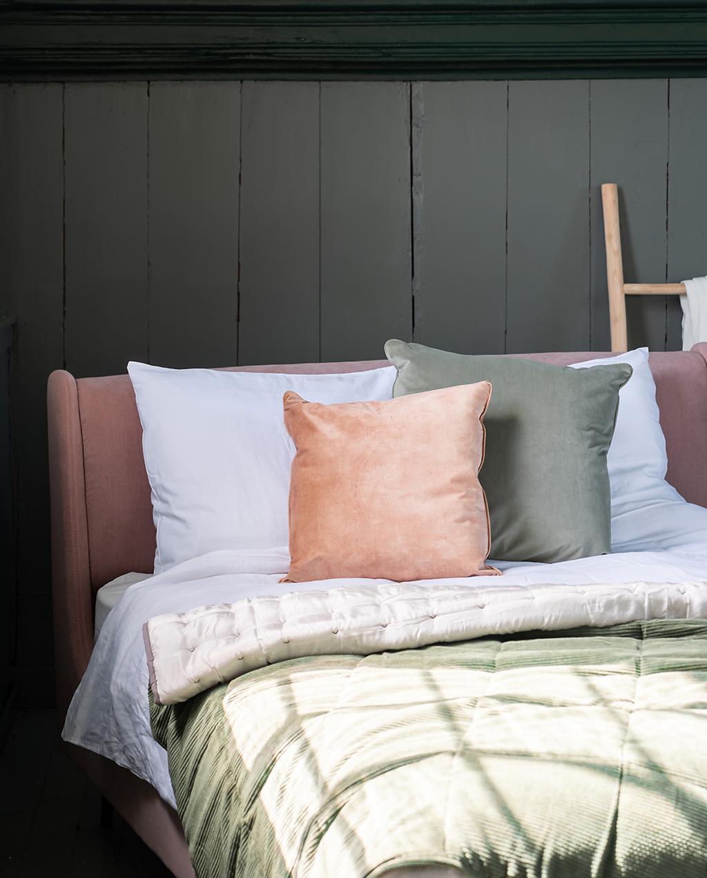 heilige nachten en made.com | overnachten in een opgeknapte kerk | roze bed met roze en groene kussens en een groene sprei