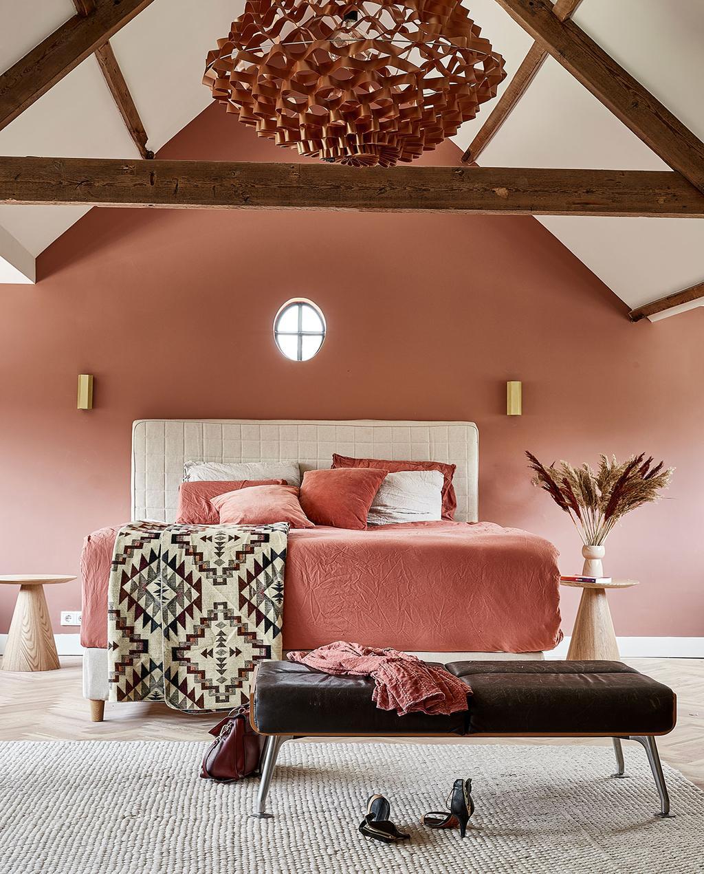 vtwonen 05-2021 | slaapkamer met schuin dak en houten balken, met een roze opgemaakt bed