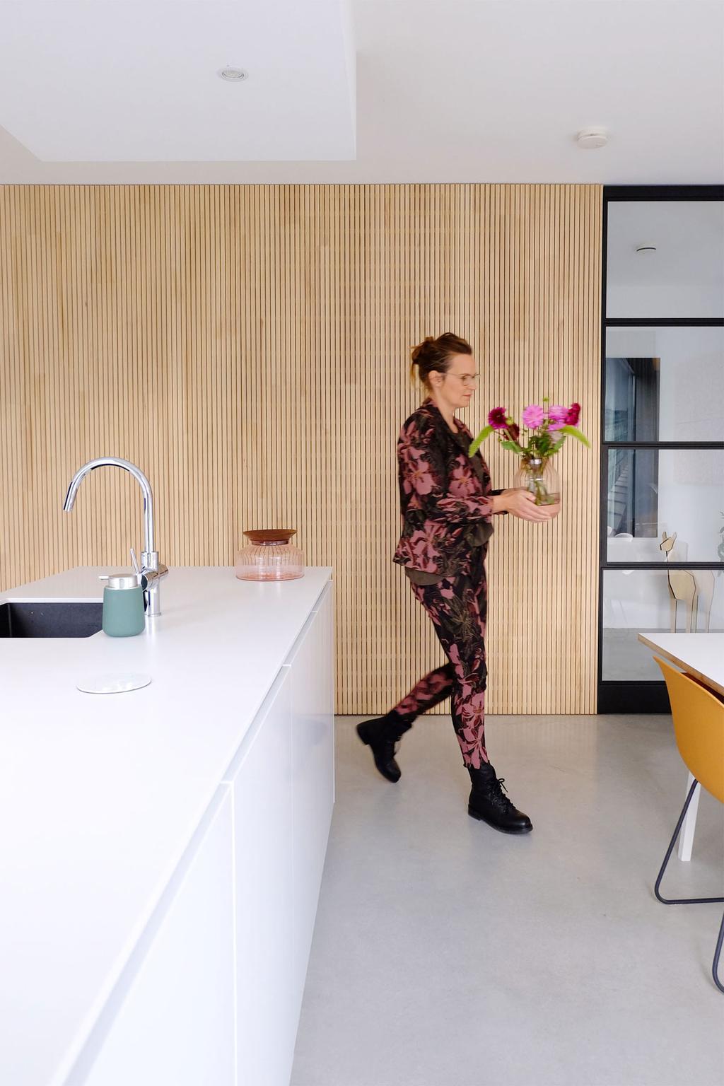 Wit kookeiland in de designkeuken van PRCHTG met houten muur.