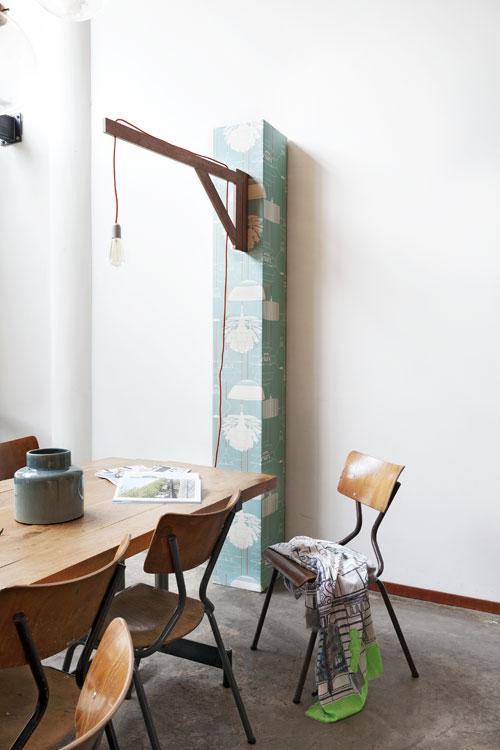 wandlamp in eetkamer met bruine, houten stoelen