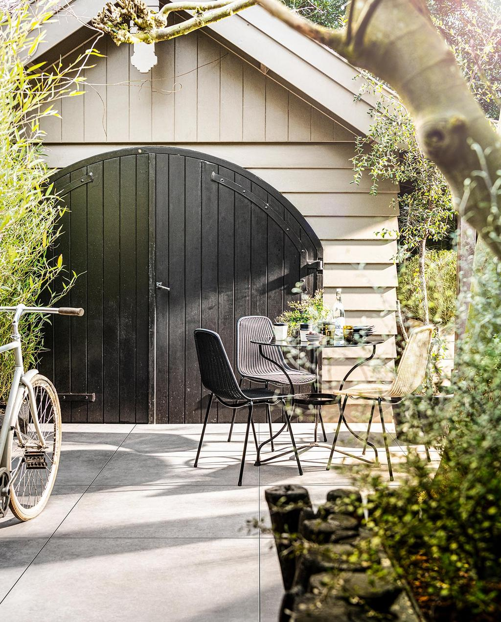vtwonen 03-2021 | schuur met fiets en tafel met nieuwe vtwonen tegels