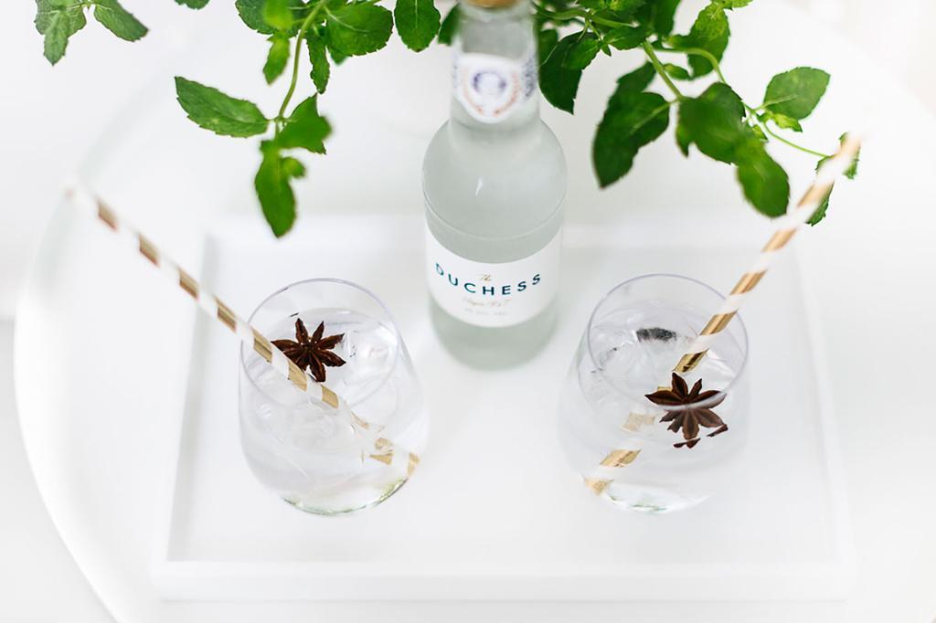 Glazen met gin & tonic staan op een wit tafeltje.