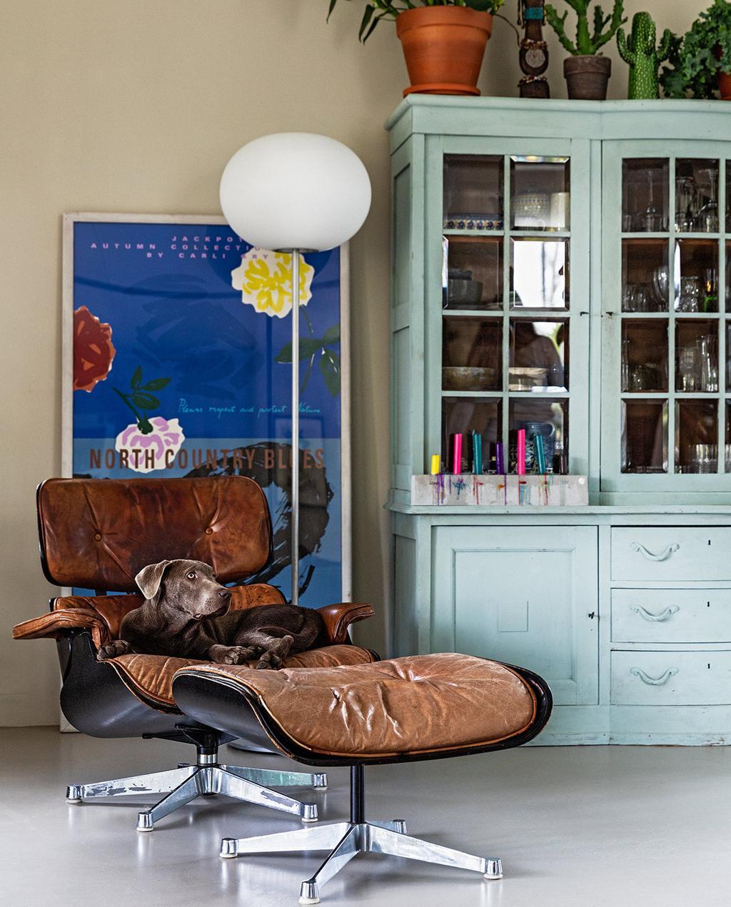 vtwonen 07-2021 | vitra Eames chair de lounge stoel voor een blauw kunstwerk en een blauwe kast | designklassiekers goede investering