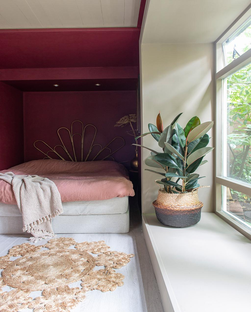 vtwonen 01-2021 | slaapkamer met roze bed met gouden hoofdeinde met een plant naast het raam