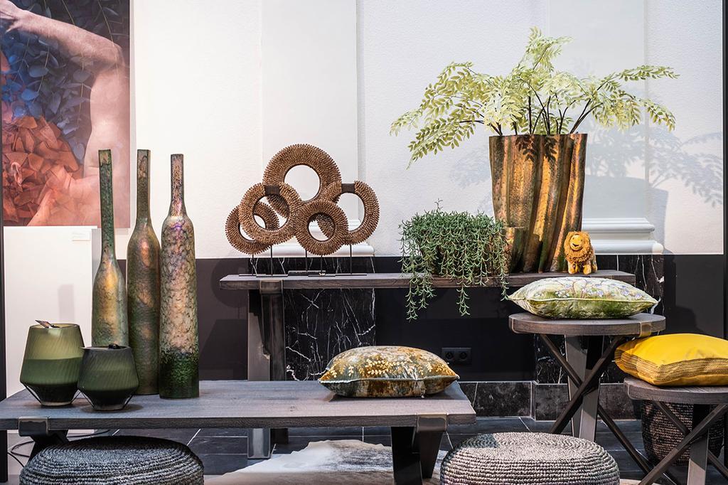 Enkele planten en decoratie staan op verschillende tafels.