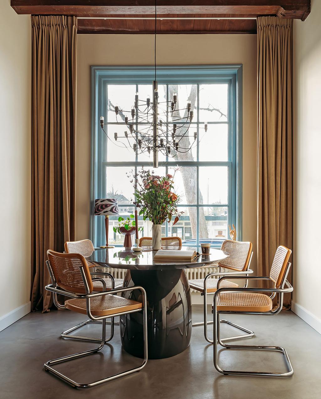 vtwonen 03-2021 | eettafel met webbing stoelen voor geverfd blauw raam en gordijnen