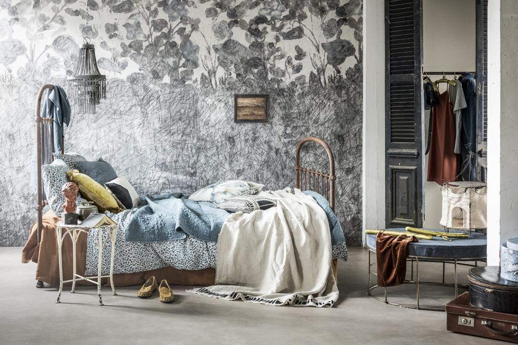 Slaapkamer uit styling wonen met lef met een brocante bed, bloemen behang en kussens en plaids met print.
