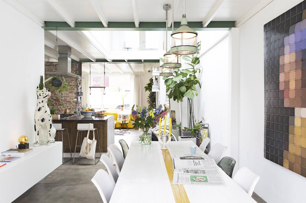Eetkamer met witte tafel en hangende plant