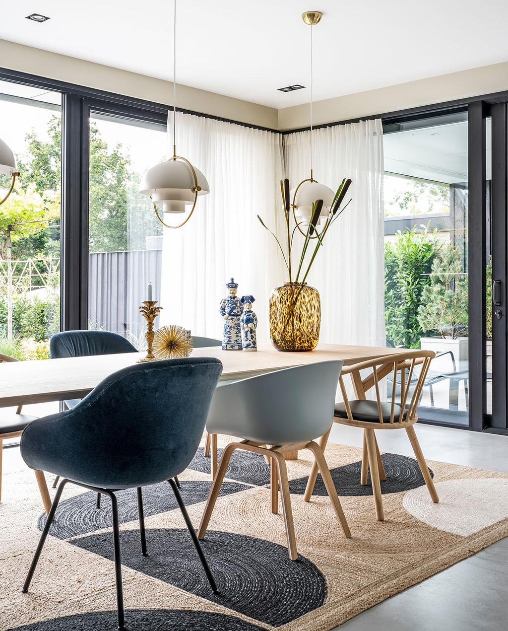 vtwonen 03-2021 | eetkamer met houten tafel en stoelen in verschillende blauwtinten | jute vloerkleed onder de eettafel