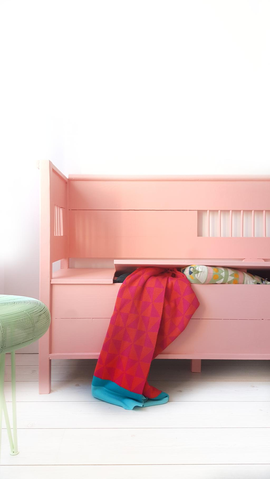 Roze bank als handige opberger én bank om op te zitten in de hal