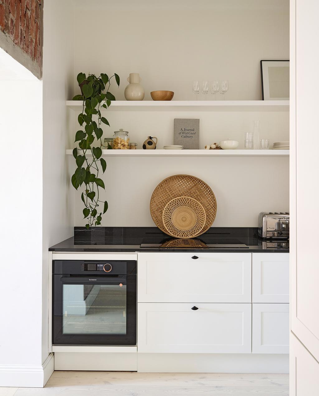 vtwonen special tiny houses | rieten manden met zwart aanrecht in de keuken