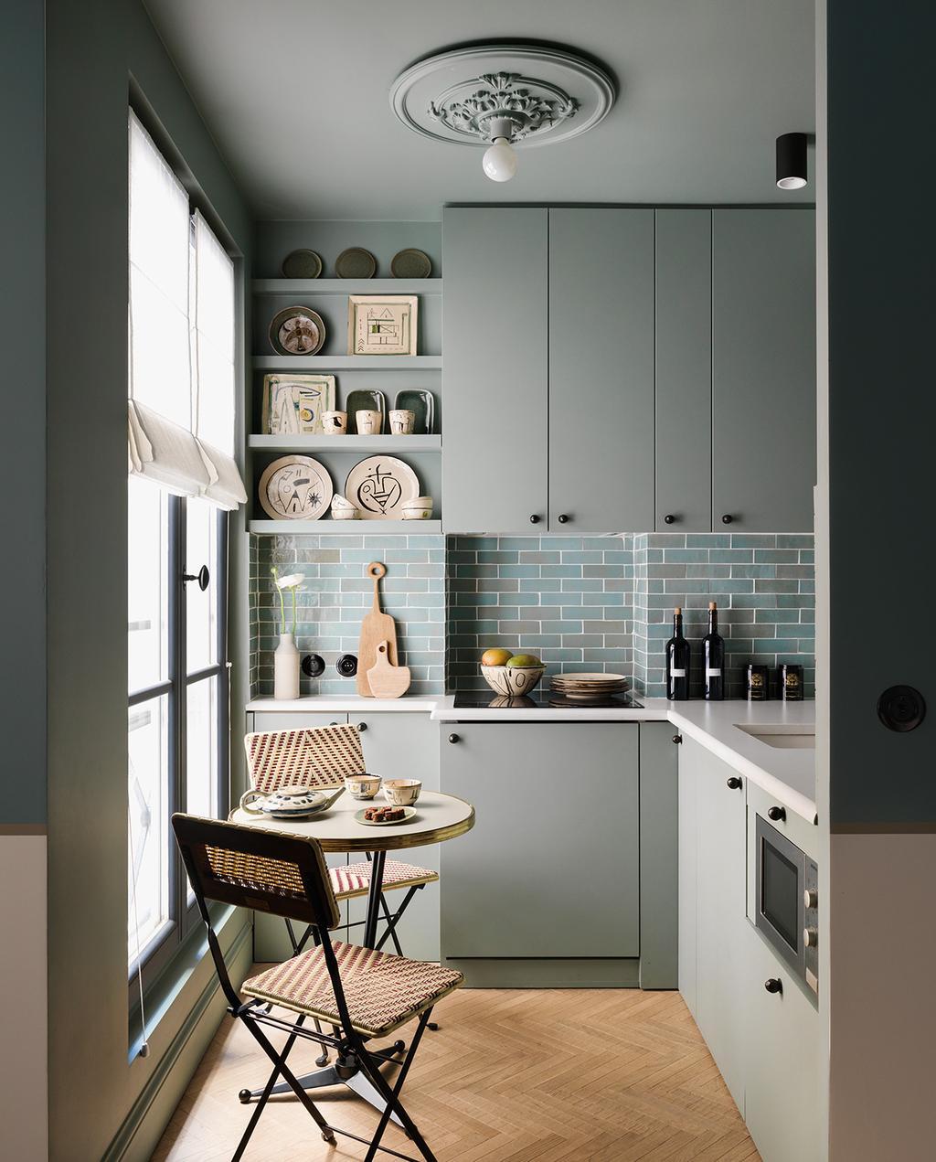 vtwonen special tiny houses | de grijs groene keuken van het appartement in het centrum van Parijs, met twee webbing stoelen en een mini ronde keukentafel