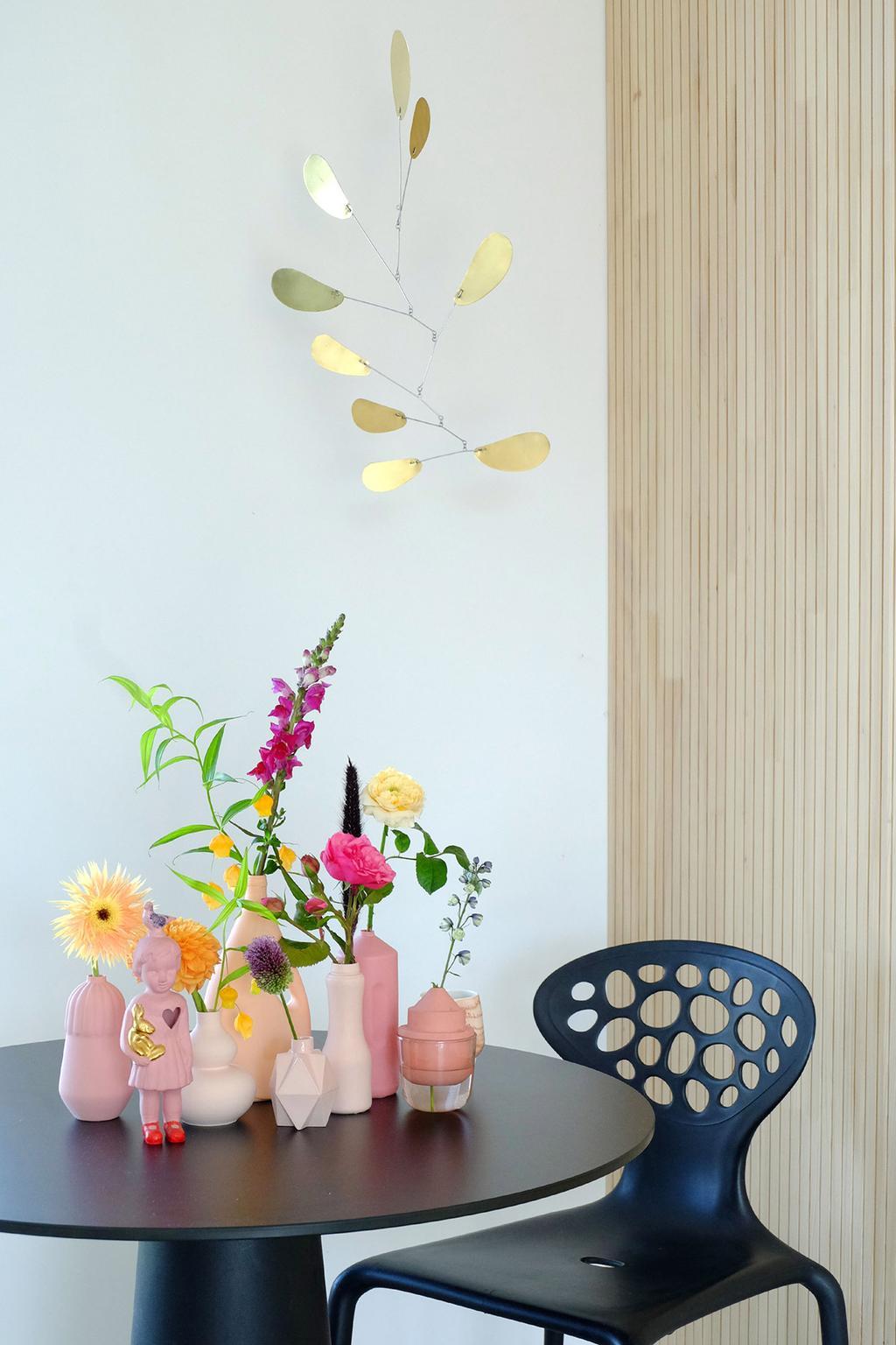 Messing mobiel van Dolly boven een tafel met keramiek