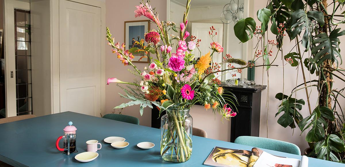 Bloomon boeket op blauwe eettafel