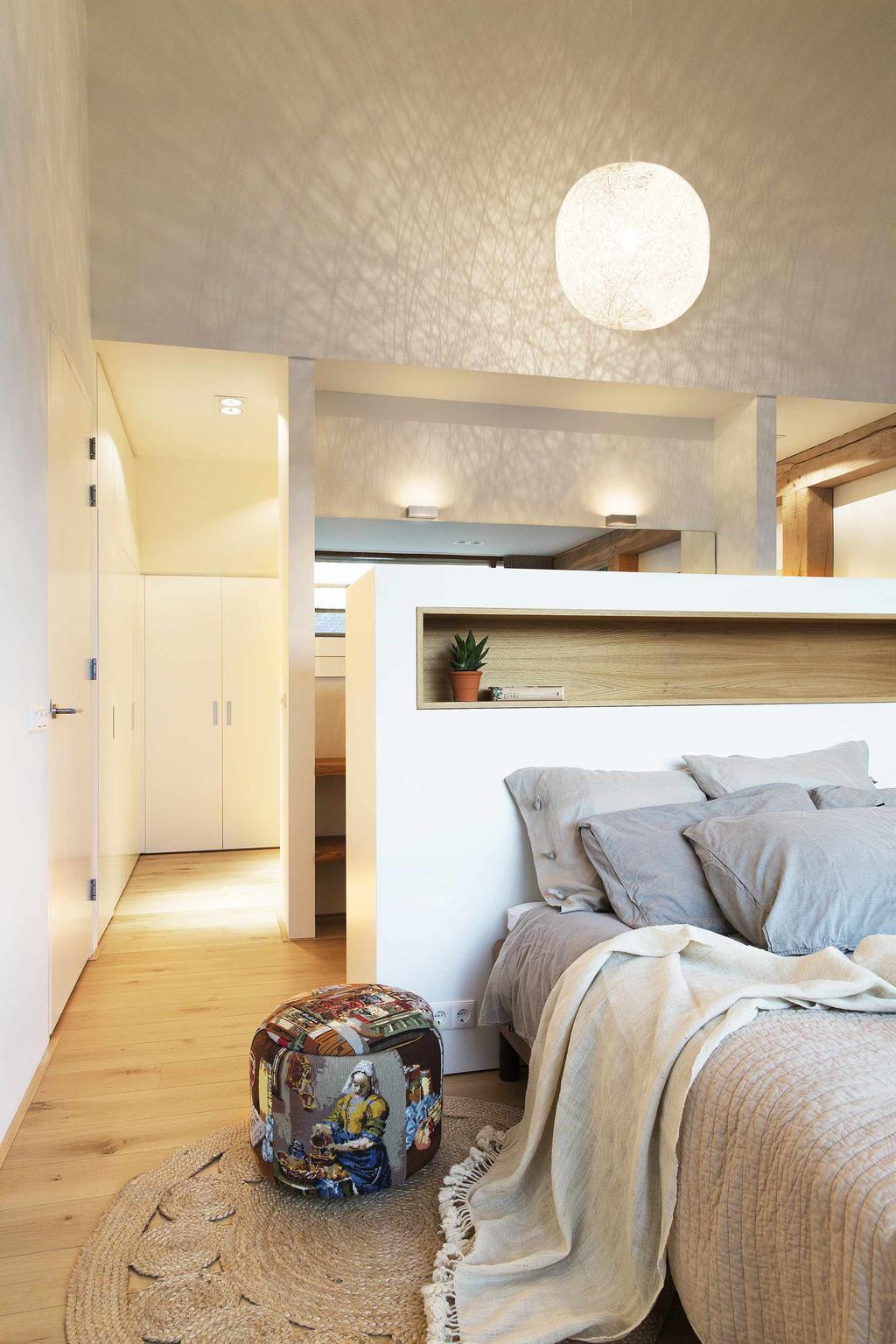 Slaapkamer met wit schot en donker dekbed