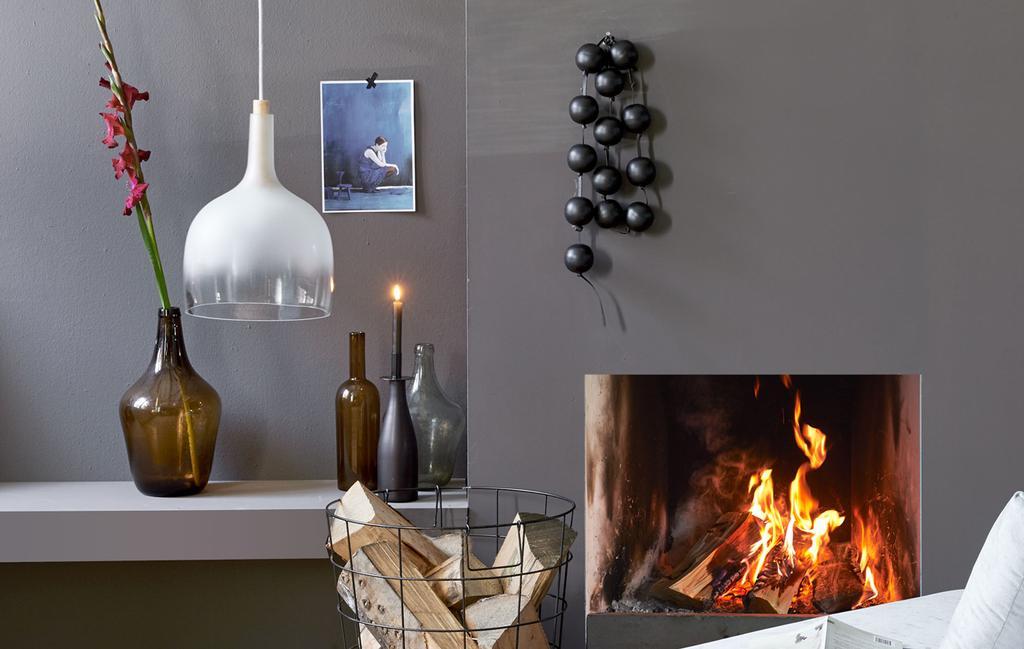 woonkamer met open haard, witte stoel, hanglamp en vaas