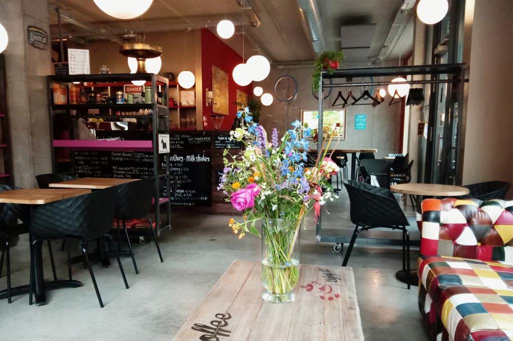 het interieur van Swartehond van Marjorie Trivick met houten tafel, bloemen en Chesterfield