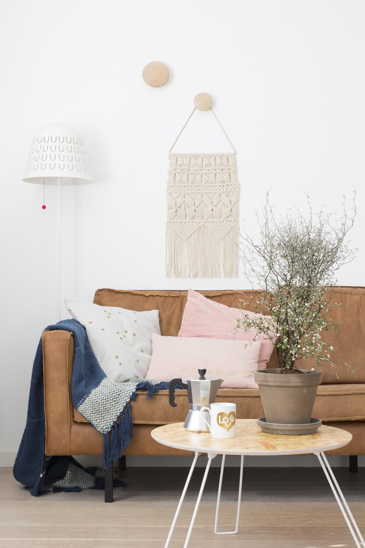 Woonkamer met kussens, wandkleed, plant en koffiemok in het voorjaarshuis van Elske