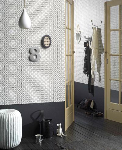 behang van ></a><br /> De donkergrijs geschilderde lage lambrisrering geeft de ruimte extra sfeer. Doordat het behang lichter is dan de onderste strook krijg je een ruimelijk effect. In een ruimte als de gang is zo'n lambrisrering naast sfeervol ook handig. De onderkant van de muur wordt in een hal vaak sneller vies door schoenen en tassen tegen de wand te plaatsen. Met speciale verf kun je de wand eenvoudig reinigen.</p> <p><strong>Behang:</strong> artikelnummer OZ 7265 van Onszelf<br /> <strong>Behangcollectie:</strong> Collection XS<br /> <strong>Afmetingen:</strong> 10 m lang x 53 cm breed<br /> <strong>Patroon:</strong> ja<br /> <strong>Soort behang:</strong> vliesbehang (makkelijk zelf te behangen, omdat de muren worden ingesmeerd in plaats van het behang)<br /> <strong>Prijs: </strong>29,95 per rol<br /> <strong>Kleur:</strong> mix van zwart en wit<br /> <strong>Meer info:</strong> <a href=