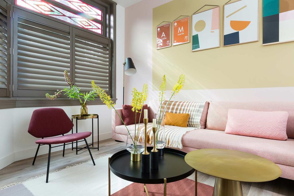 Woonkamer met roze bank tegen een wand met geel kleurvlak en vrolijke schilderijen