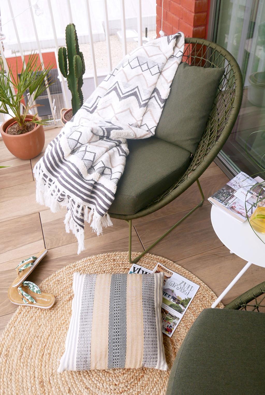 Een groene stoel met een wit deken staat op een terras.