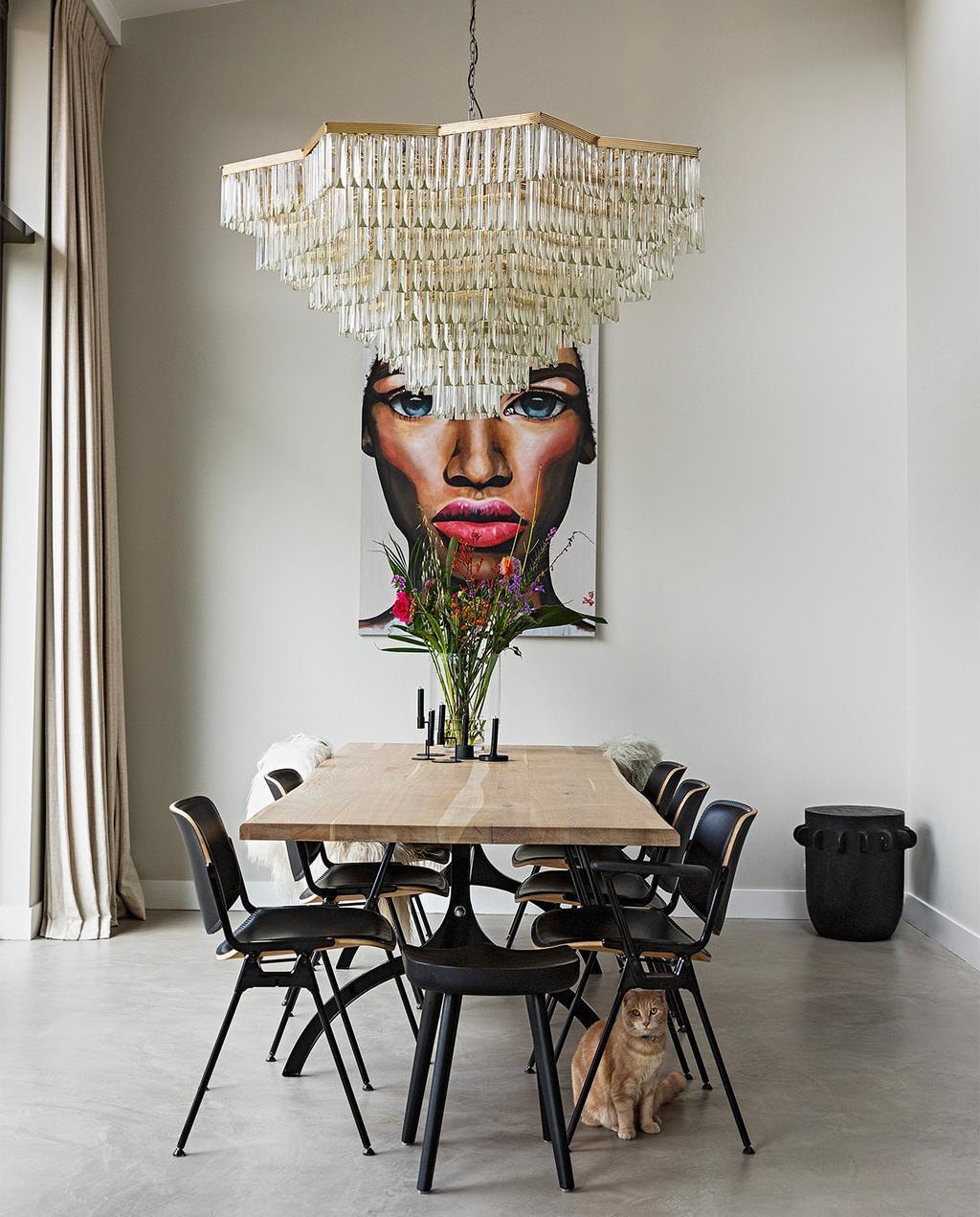 vtwonen 08-2021 | eettafel met plek voor negen personen en een grote kandelaar, met op de achtergrond een schilderij van een vrouw