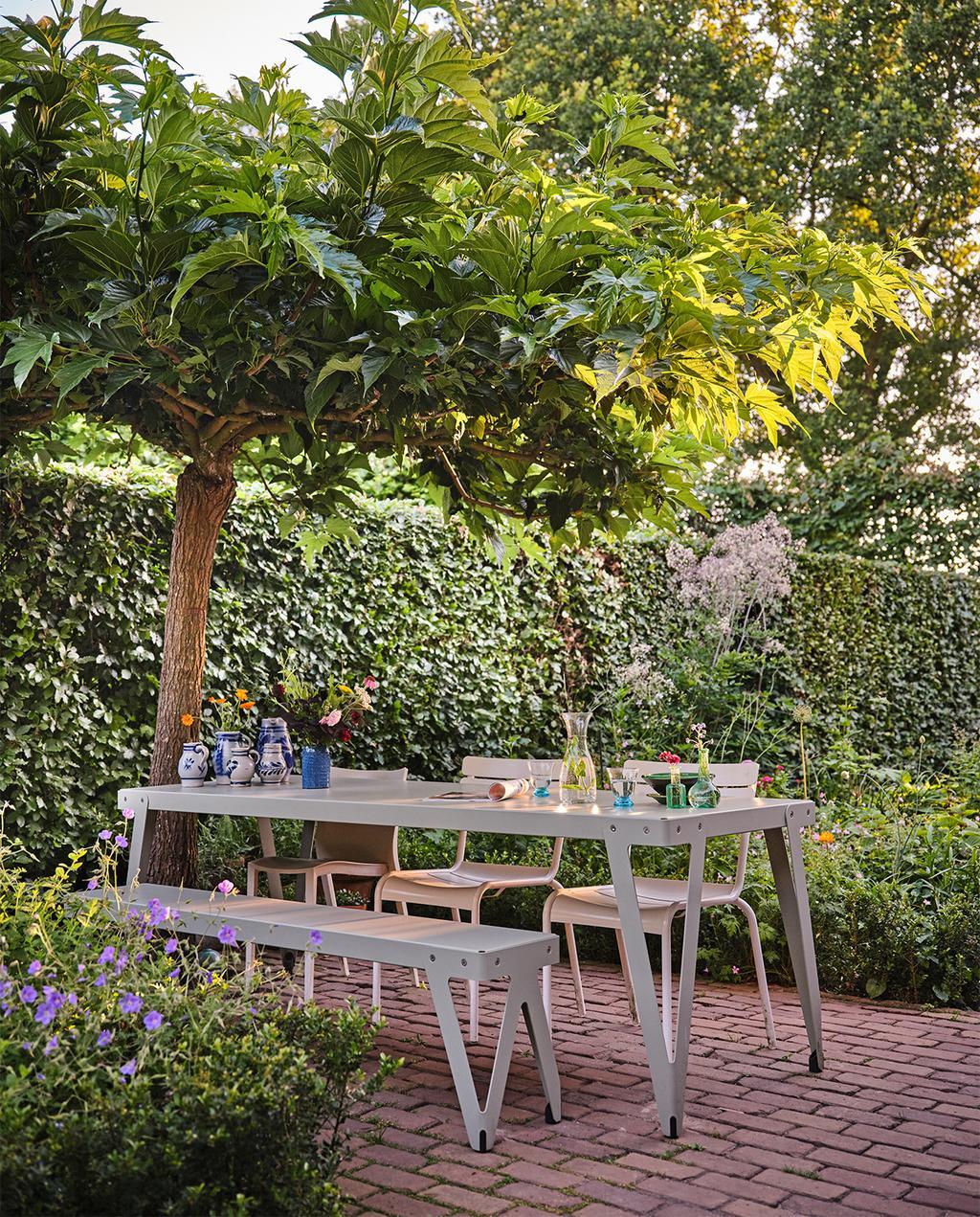 vtwonen tuin special 3 2021 | eettafel in de tuin met een bankje en twee stoelen