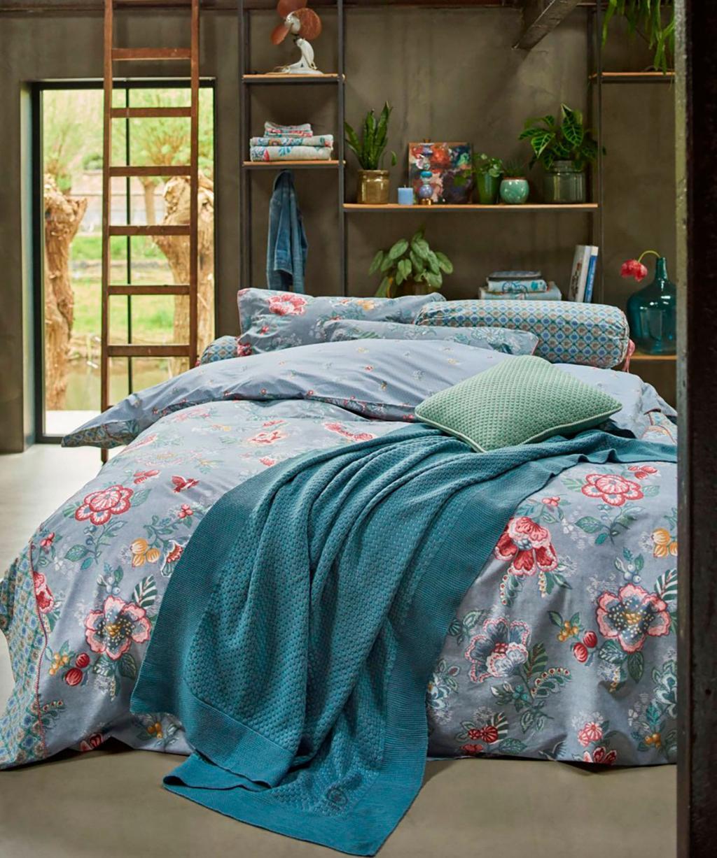Een blauw bed in een tienerkamer van een meisje.