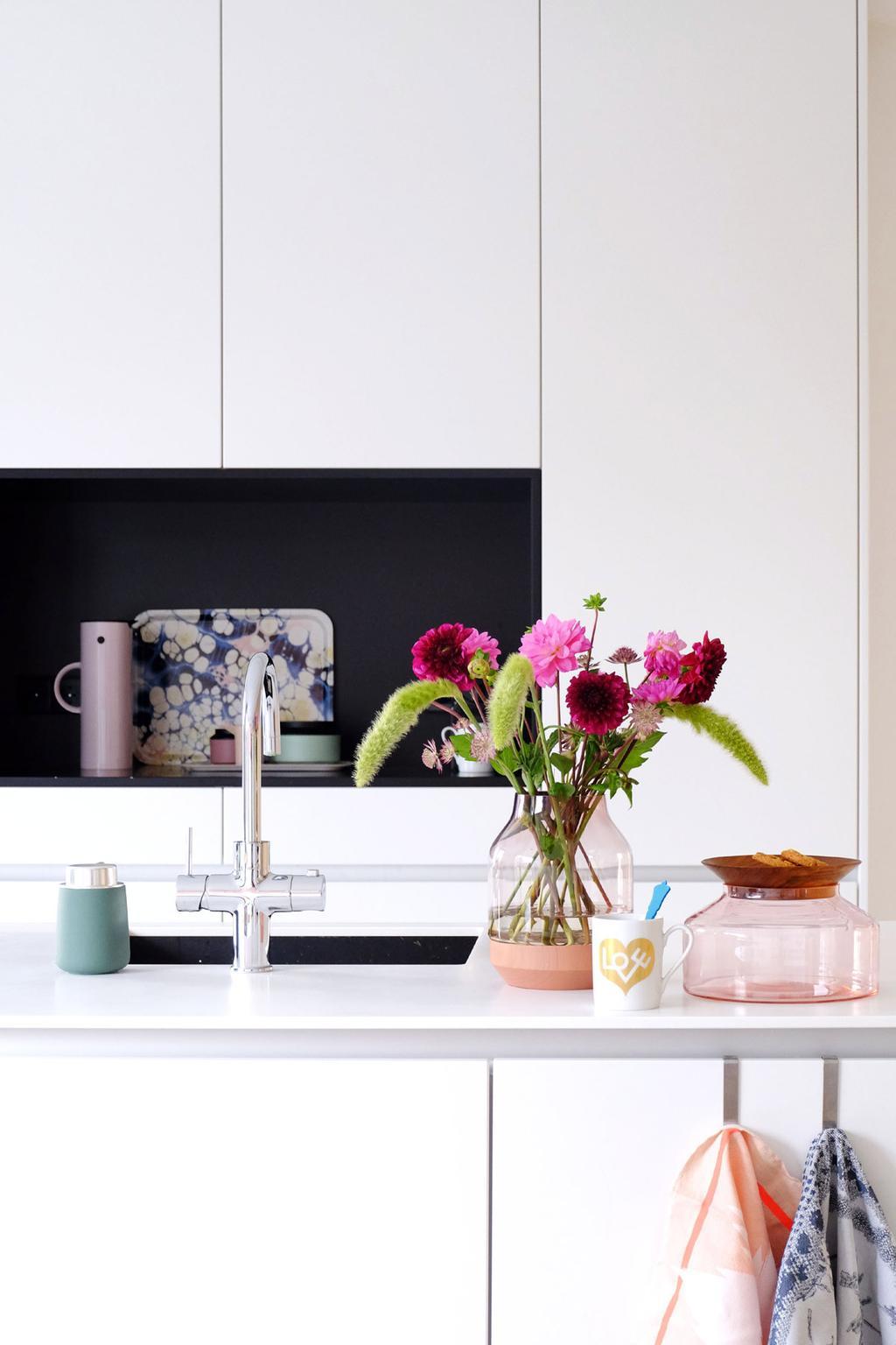 Witte greeploze designkeuken van PRCHTG met kleurrijke accessoires.