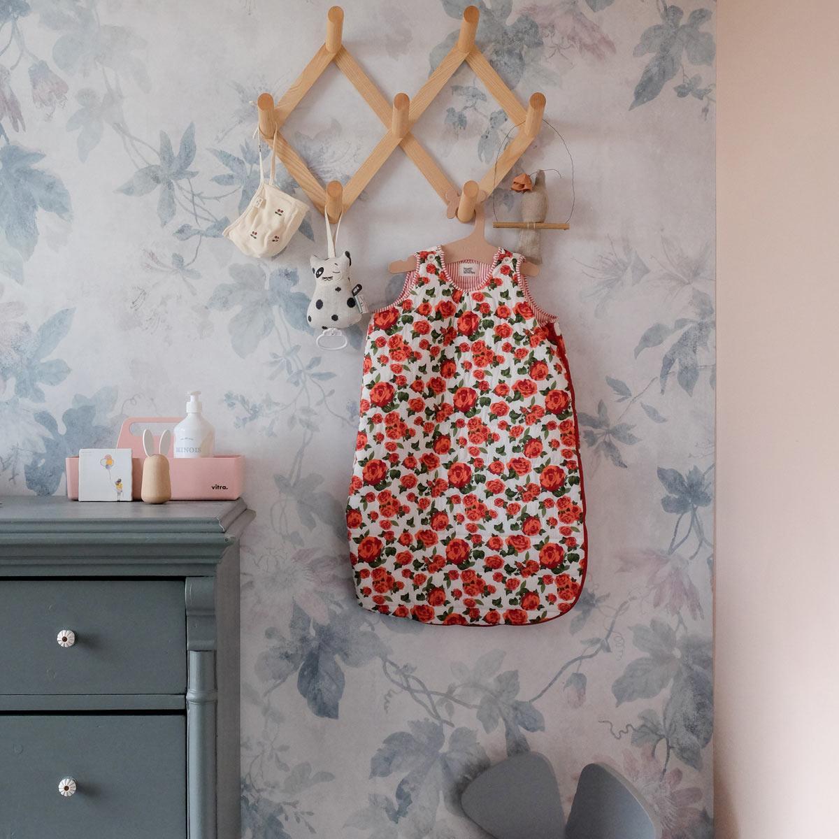 Babykamer met gebloemd behang en vrolijke kleuren.