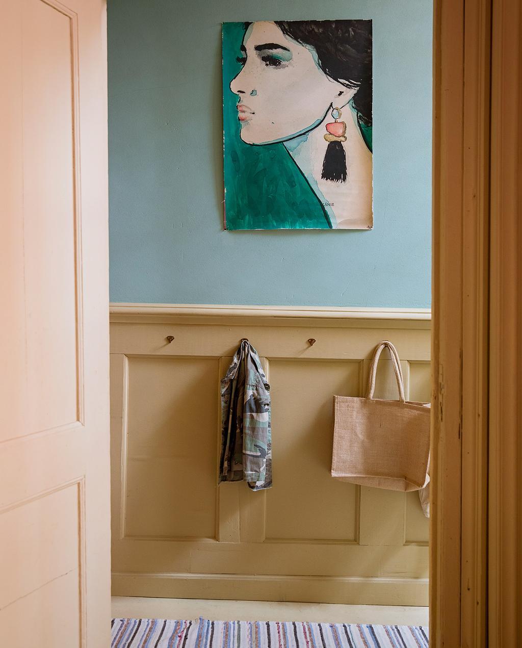 vtwonen 06-2021   gang met gele lambrisering en blauwe muur en schilderij van vrouw met oorbel