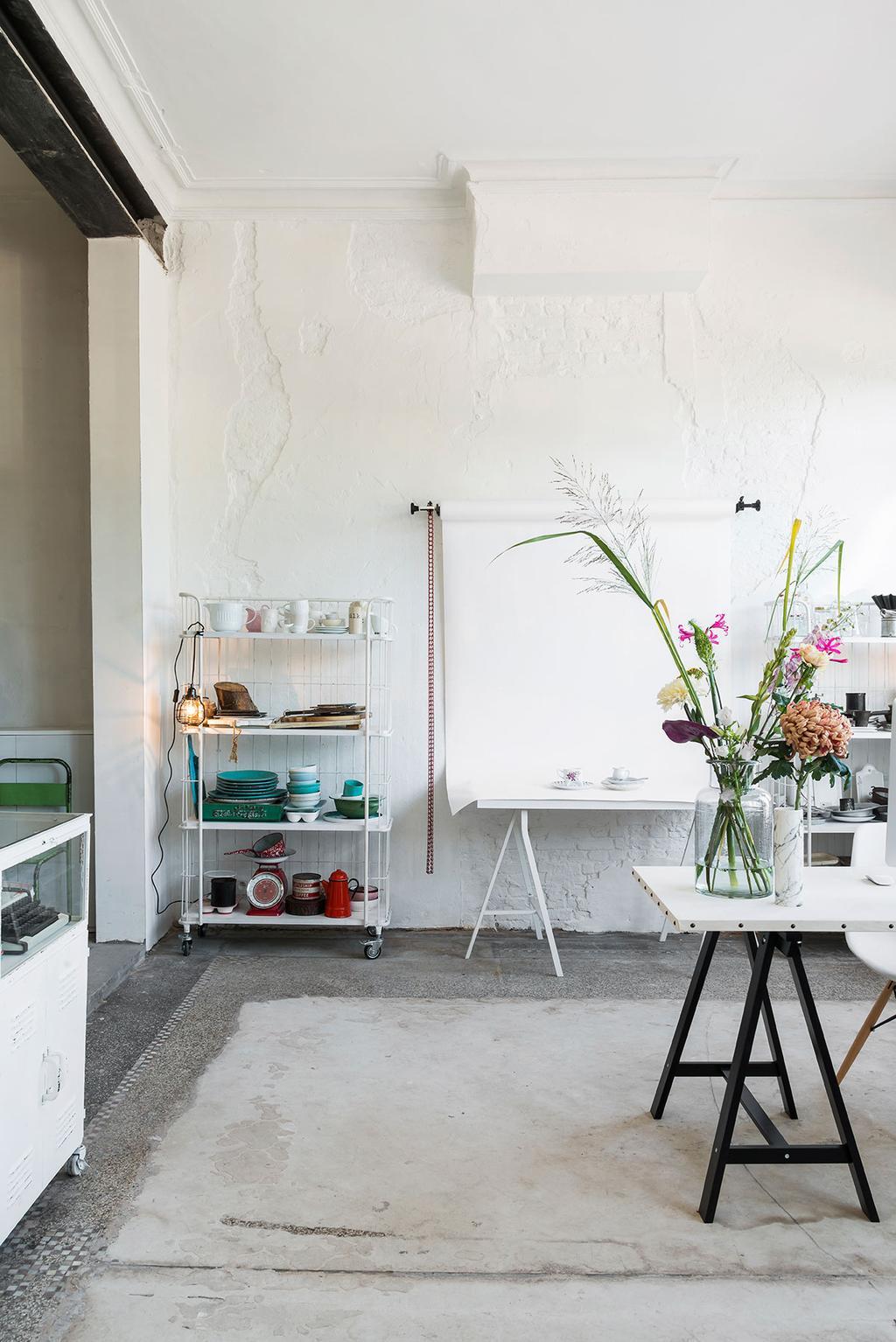 Boeket bloemen op bureau met schragen en witte muren