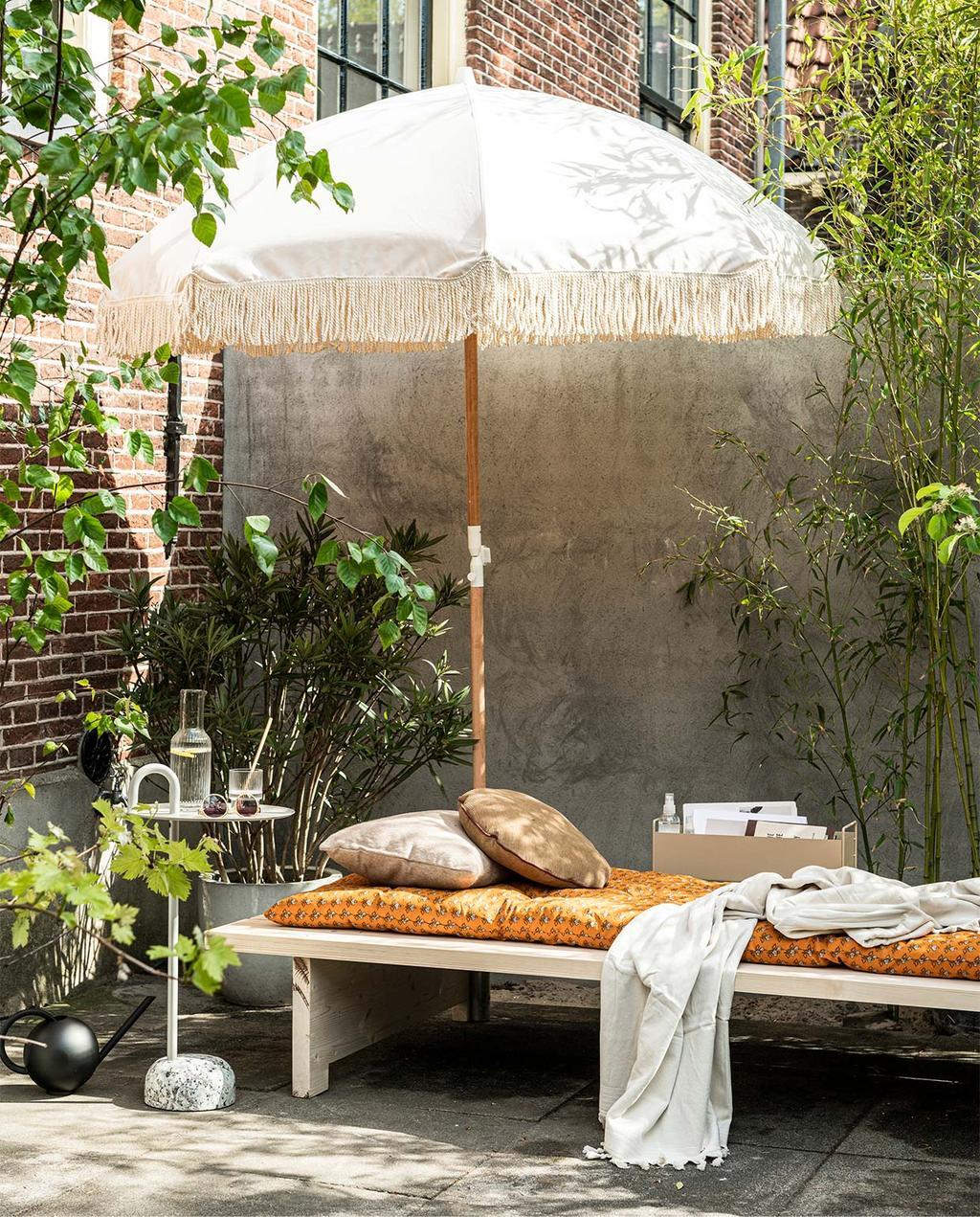 vtwonen 06-2020 | witte parasol en een loungebed met een oranje kussen