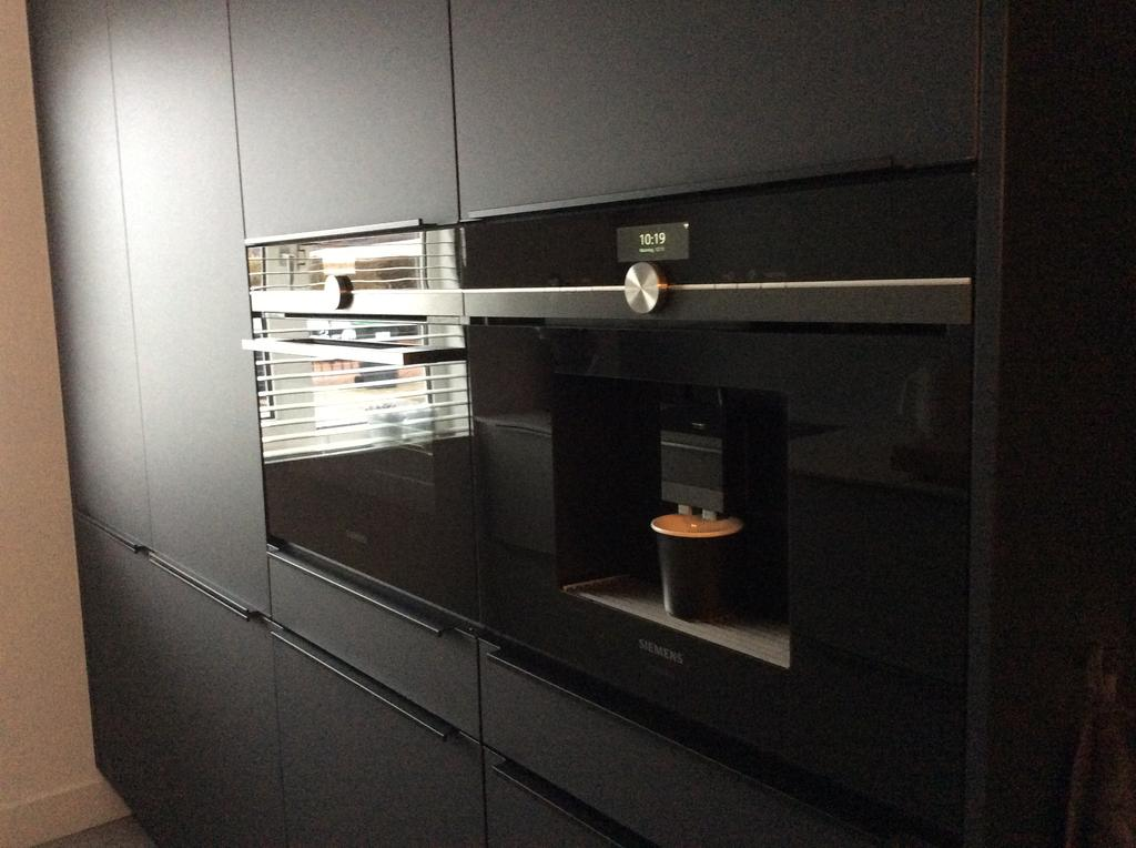 zwarte-keukenwand-met-benodigde-apparatuur-koffiemachine-en-een-stoom-bak-oven-beide-van-siemens-geeft-de-heerlijkste-koffie