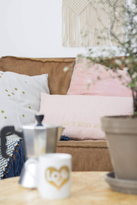 Roze kussentjes en kussen met stip op de bank in het voorjaarshuis van Elske