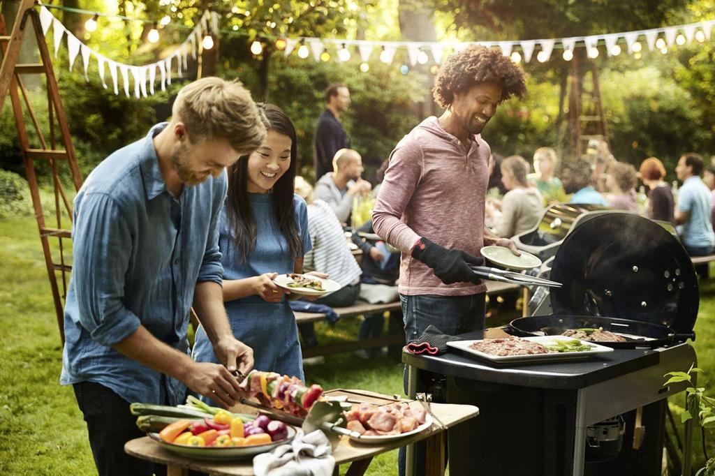 Vrienden terwijl ze aanschuiven voor de barbecue in een gezellige tuinsetting
