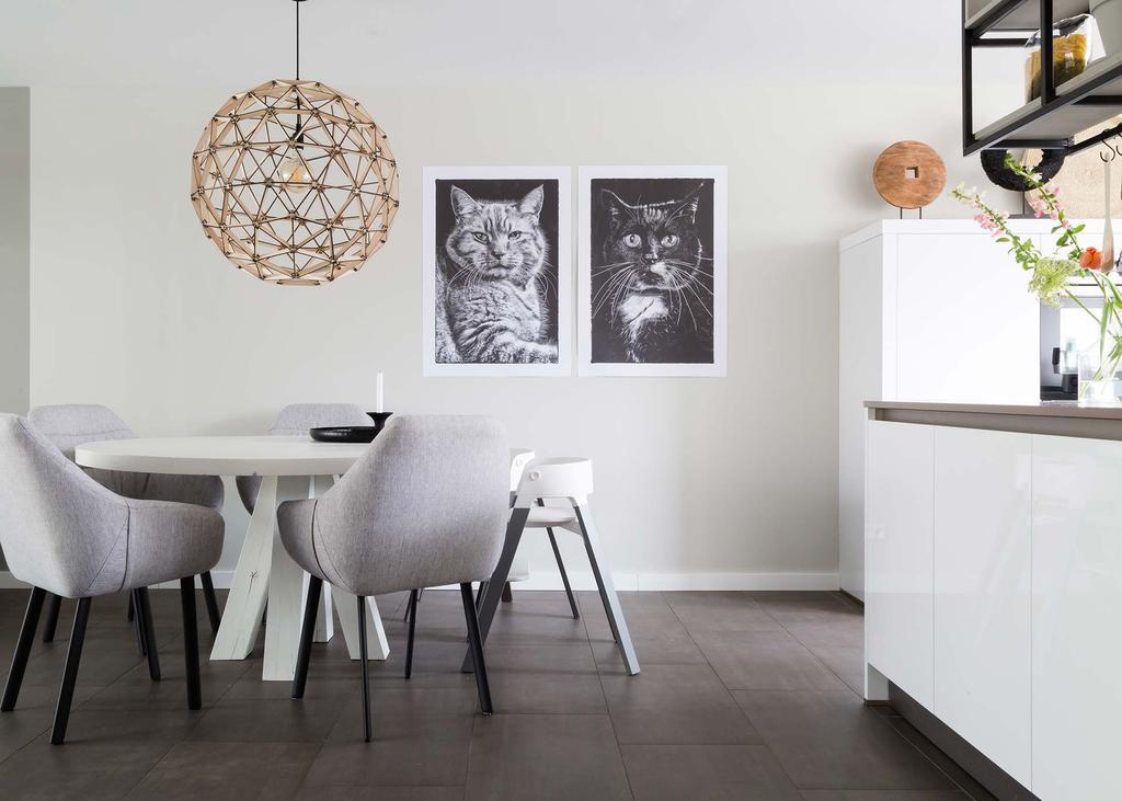 Neutrale eethoek met ronde eettafel en stoere katten posters
