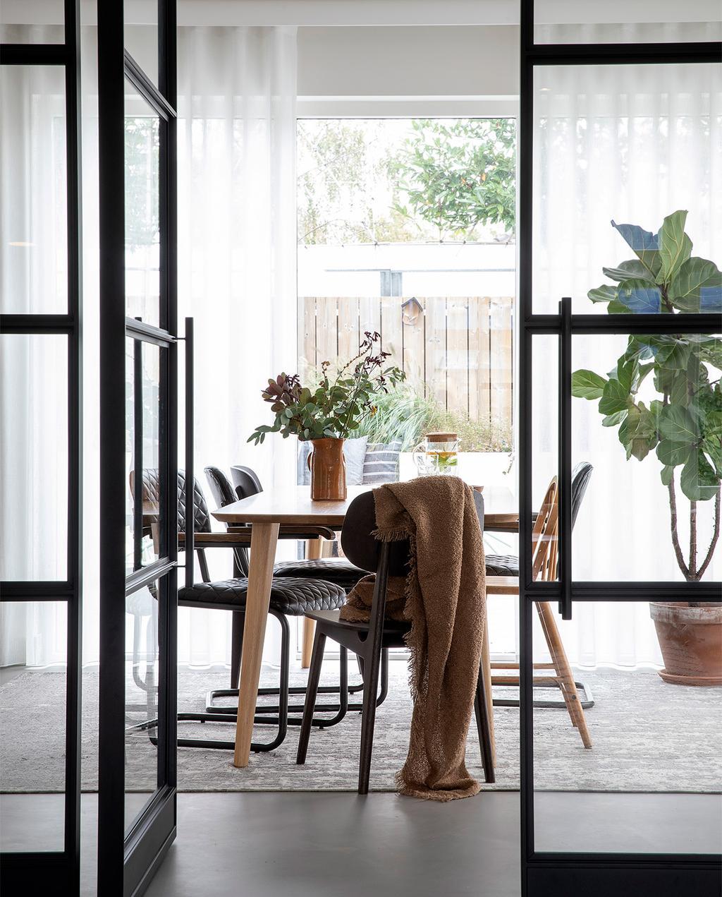 vtwonen 08-2021 | zwarte deur bij eetkamer met houten tafel en stoelen