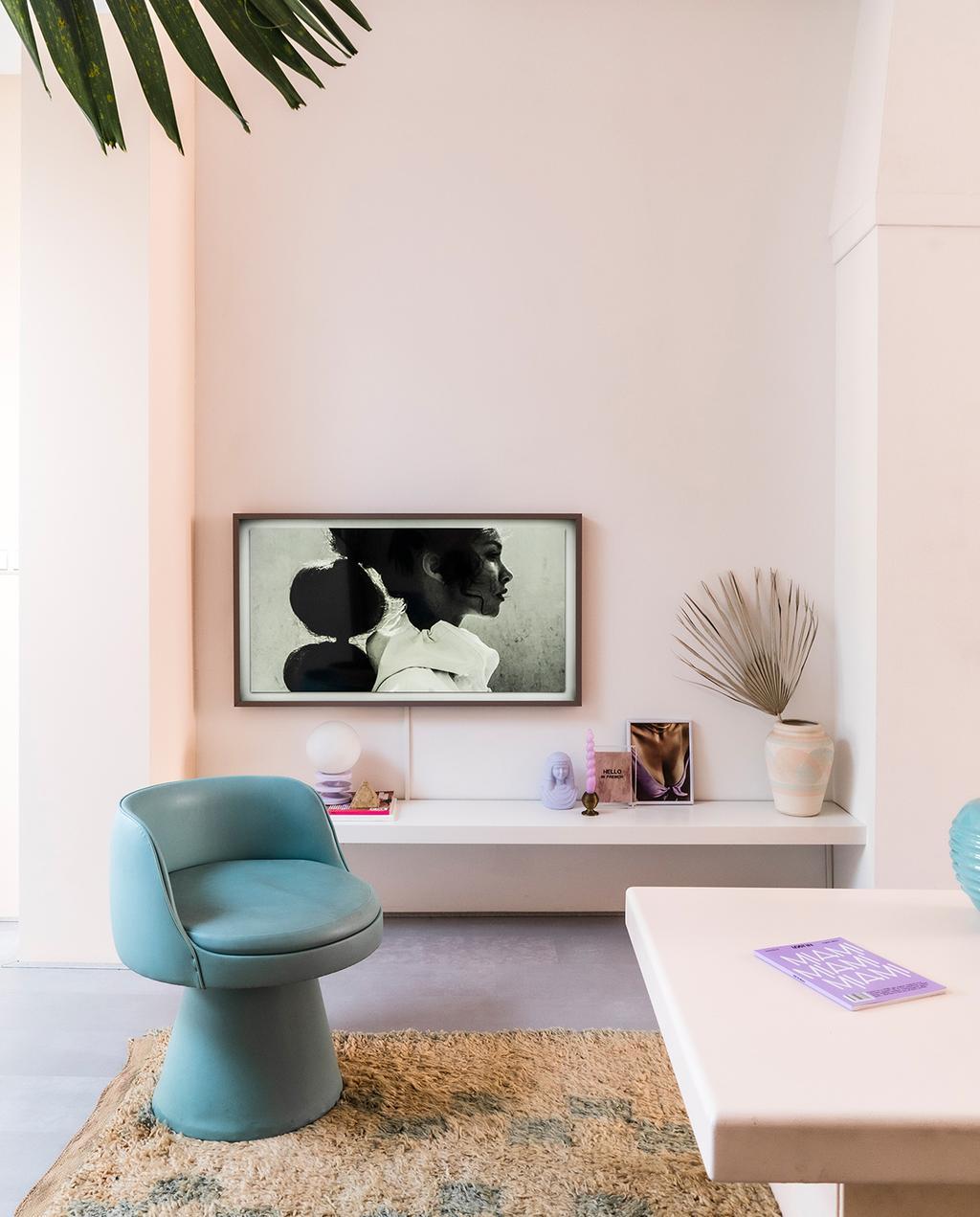 vtwonen 06-2021 | blauwe fauteuil en vloerkleed met kunstwerk op de achtermuur