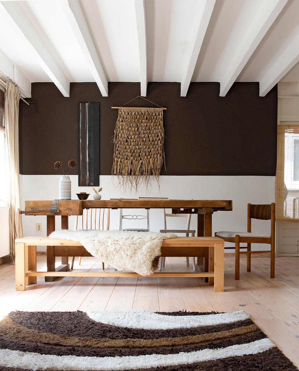 vtwonen 08-2021 | bruine lambrisering voor de houten eettafel, met een bruin vloerkleed op de grond