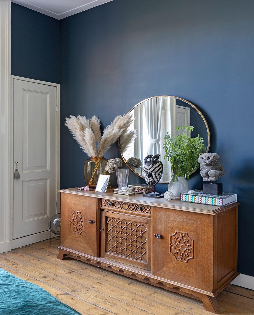 vtwonen 01-2021 | binnenkijken bij interior junkie houten kast met ronde spiegel en pluimen, blauw geverfde muur