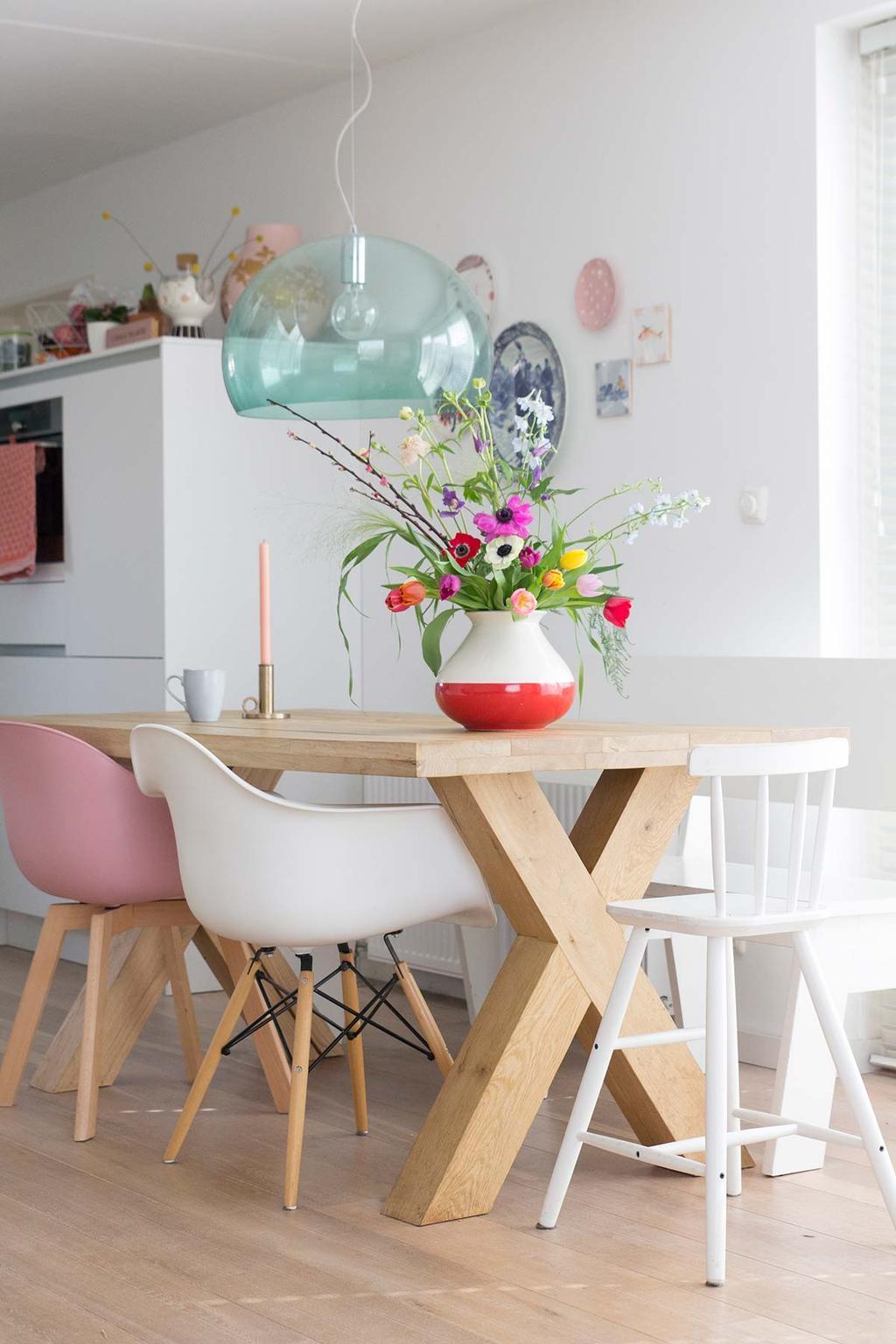 Voorjaarsbloemen in vaas op een houten eettafel