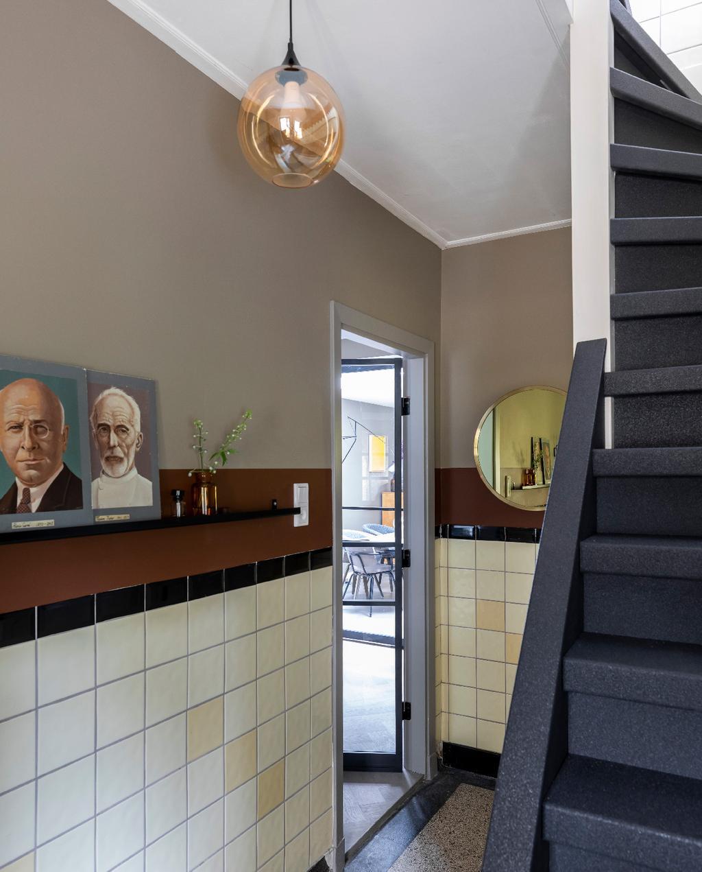vtwonen weer verliefd op je huis | flexa trendkleur brave ground neutrale tinten en kleurvlakken in hal met witte tegels en zwarte trap