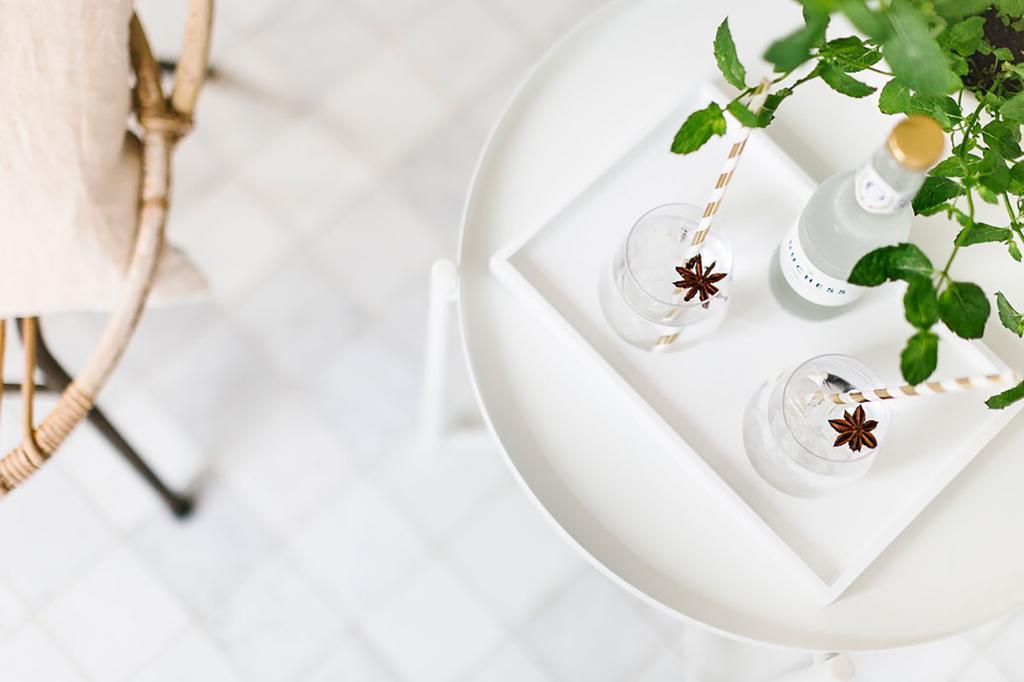 Twee gin tonics staan op een wit tafeltje naast een rotan stoel.