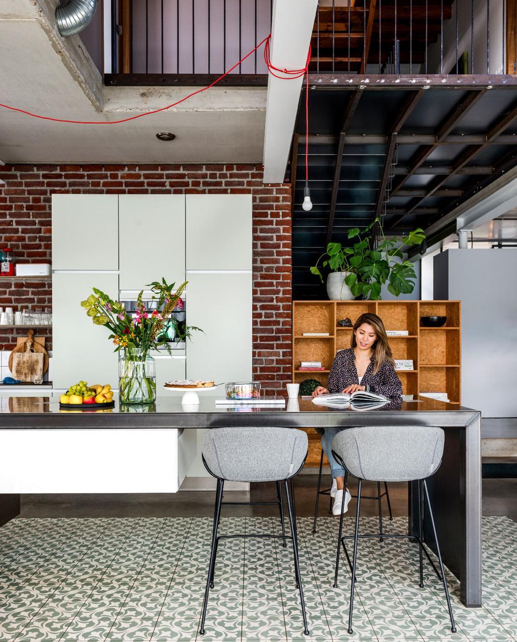 vtwonen 07-2020 | binnenkijken in Weert industriele keuken met rvs kookeiland en bakstenen muur