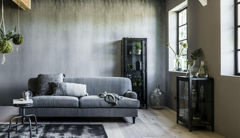 woonkamer met grijze bank zwarte kast en grijze muur