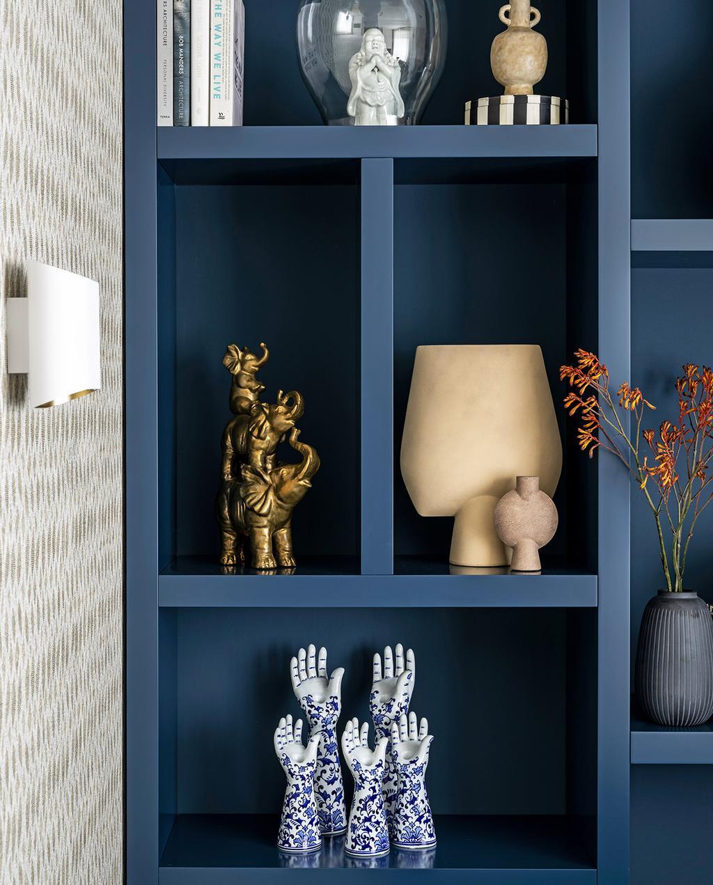 vtwonen 03-2021 | vakkenkast met pols potten vaas en verschillende ornamenten in blauwtinten